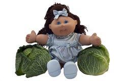 Bambola del giocattolo che si siede fra due cavoli Immagine Stock Libera da Diritti