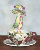 Bambola del pagliaccio di Pierrot che equilibra su una tazza di tè Immagine Stock