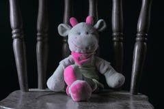 Bambola della mucca che si siede su una sedia di legno immagini stock