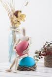 Bambola di legno che tiene l'uovo di Pasqua su fondo bianco Immagine Stock Libera da Diritti