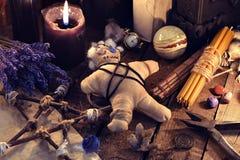 Bambola di voodoo, pentagramma ed oggetti di magia sulla tavola della strega immagine stock