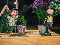 Bambola e fiore dell'agricoltore della ragazza e del ragazzo sulla tavola Fotografie Stock