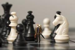 Bambola miniatura e scacchi Viaggiatore anziano in scacchiera Immagine Stock