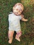 Bambola rotta ed abbandonata nell'erba Immagine Stock Libera da Diritti