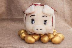 Bambola sveglia del maiale sull'uovo di Pasqua dorato Fotografie Stock