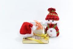 Bambola sveglia del pupazzo di neve su fondo bianco con il cappello ed il regalo rossi, giocattolo per natale Fotografia Stock