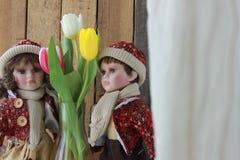 Bambola in un vestito rosso ed in tulipani fotografie stock libere da diritti