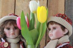Bambola in un vestito rosso ed in tulipani fotografie stock