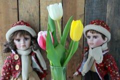Bambola in un vestito rosso ed in tulipani immagine stock libera da diritti
