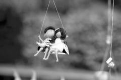 Bambole del bambino sulle oscillazioni Immagini Stock