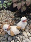 Bambole dell'anatra sulla pietra al giardino Fotografia Stock