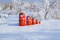 Bambole di legno russe sulla neve Immagine Stock