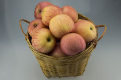Bamboo basket with apple. A bamboo woven baskets, putting a lot of beautiful delicious apple Royalty Free Stock Photo