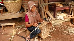 Bamboo basket craftswoman while doing his work royalty free stock photo
