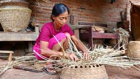 Bamboo basket craftswoman while doing his work royalty free stock image