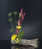 Bamboo basket decorated with bouquet of flowers Stock Photo