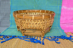 Bamboo basket. Handmade woven bamboo basket and cotton clothes background Royalty Free Stock Image