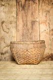 Bamboo basket on mat weave and wood board background. Picture stock image