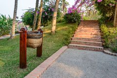 Bamboo basket use for keep garbage near walkpath in garden Royalty Free Stock Photo