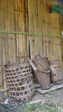 Bamboo baskets lean on latch wall Stock Photos