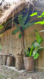 Bamboo baskets lean on latch wall Stock Image