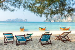 Bamboo beach chairs and traditional long-tail boats Royalty Free Stock Photo