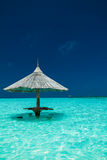 Bamboo beach umbrella with bar seats in the water of an island Stock Photo