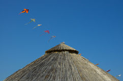 Bamboo beach umbrella and kites over a blue sky. Bamboo beach umbrella and sequence of kites over a blue sky Royalty Free Stock Image