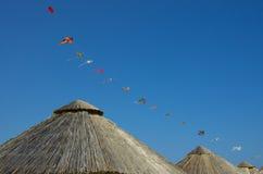 Bamboo beach umbrella and kites over a blue sky. Bamboo beach umbrella and sequence of kites over a blue sky Stock Image