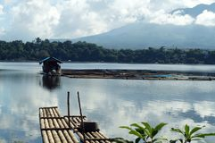 Bamboo boat rafts anchored at mountain lake shore on a cloudy day. Sampaloc Lake, San Pablo City, Laguna, Philippines - November 9, 2017: Two 2 bamboo boat rafts Stock Photography