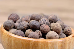 Bamboo bowl with allspice. On brown background stock photo
