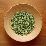 Bamboo Bowl with Green Peas on Wood Background Stock Photos