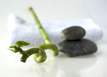 Bamboo branch with stones and towel Stock Photos