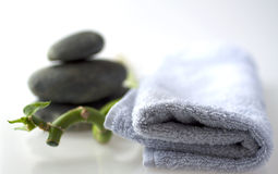 Bamboo branch with stones and towel Royalty Free Stock Photos