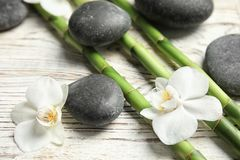 Bamboo branches, spa stones and flowers. On wooden background royalty free stock images