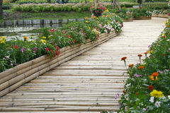 Bamboo bridge with flower. On the pond Stock Images
