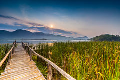 Bamboo bridge near reservoir with mountain and sky view Stock Image