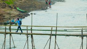 Bamboo bridge over a small river. Convenient way for tourists stock video