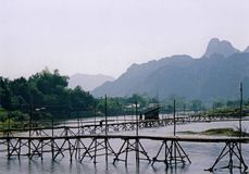 Bamboo bridge vang vieng river laos. Network of wooden bridges crossing wide river in vang vieng laos with karst mountains in background stock photos