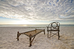 Bamboo Chair and Camp Bed Sitting on Sandy Beach Royalty Free Stock Image