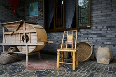 Bamboo chair and wooden thresher outside farmhouse Royalty Free Stock Photography