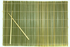 Bamboo chopsticks and mat Stock Images