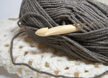 Bamboo Crochet hook in brown yarn. Large wooden bamboo Crochet hook is featured in brown yarn atop crocheted white fabric Royalty Free Stock Image