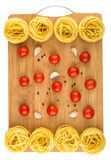 Bamboo cutting board with fettuccine pasta, tomatoes and garlic Stock Photo