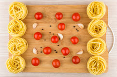 Bamboo cutting board with fettuccine pasta, tomatoes and garlic Royalty Free Stock Image
