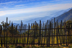 Bamboo fence in rural field with beautiful natural mountain land Stock Photography