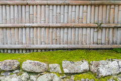 Bamboo fence on stone with green leaves  . Stock Images