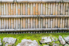 Bamboo fence on stone with green leaves  . Royalty Free Stock Photo