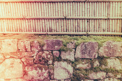 Bamboo fence on stone with green leaves  . ( Filtered image proc Royalty Free Stock Photography