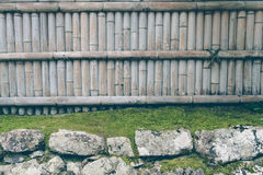 Bamboo fence on stone with green leaves  . ( Filtered image proc Royalty Free Stock Photo